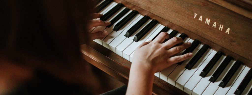 Student practicing piano during a lesson
